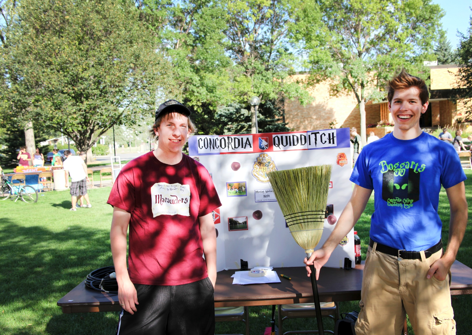 Photo by Ryan McCaughtry. Nathan Rodenberg and Russell Wustenberg, the captains of the two Quidditch teams on campus, show off their brooms and table at the Cobber Expo.