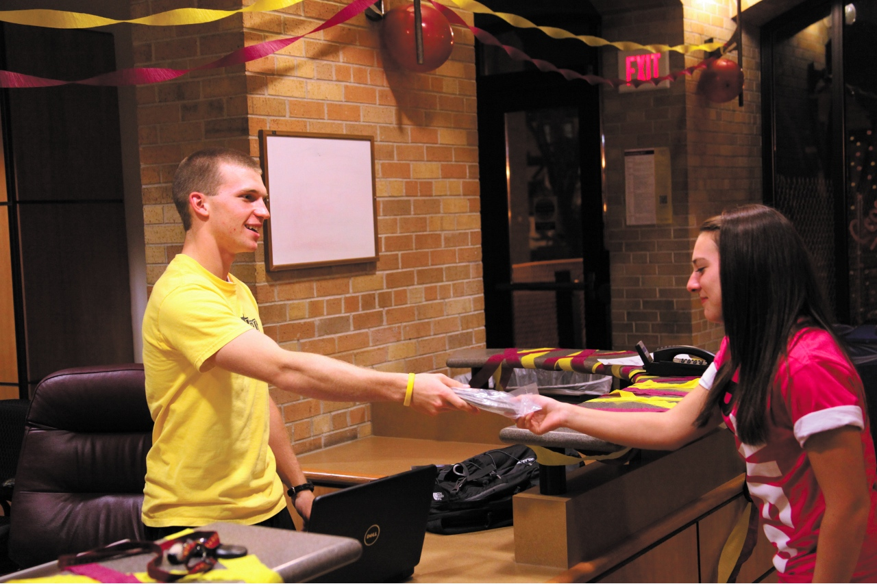Photo by Ryan McCaughtry. Levi Bachmeier (left) hands an Ethernet cable to Carly Grandner at the East Complex desk. Residence Life and ITS purchased cables for on campus residents to less the burden on the wireless connection.