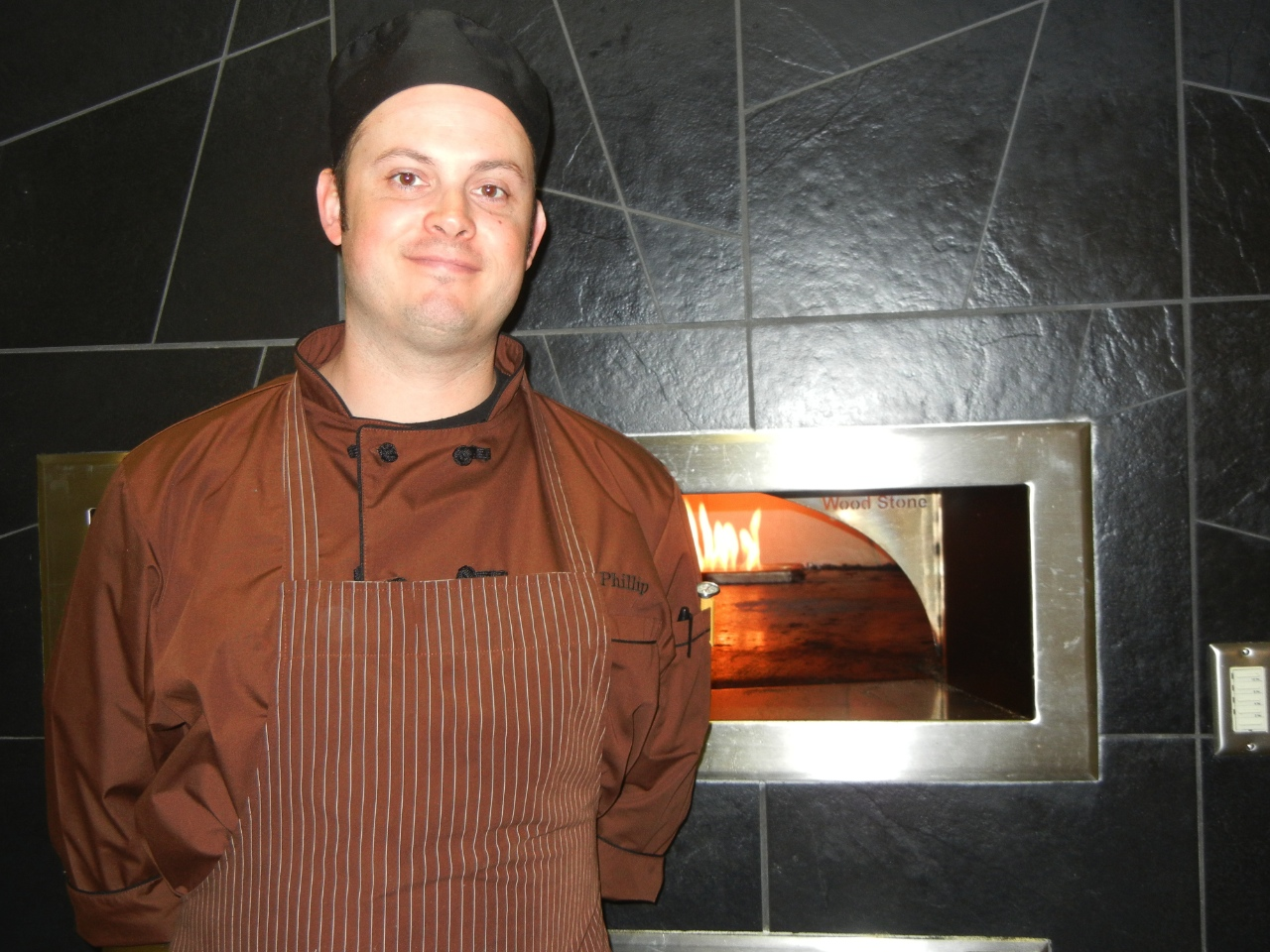 Photo by Marisa Jackels. New Head Chef Philip Edwards poses in front of the Slice Station's pizza oven.