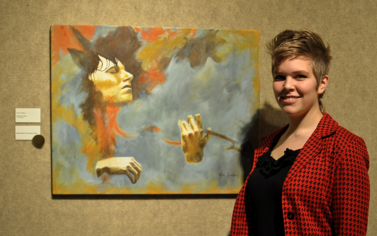 "Photo by Kyle Thiele. Senior Emily Swedberg poses in front of her oil painting, ""Emerging Tones."" This piece won the Department Purchase award, meaning it was chosen by the art faculty and purchased to be displayed on campus."