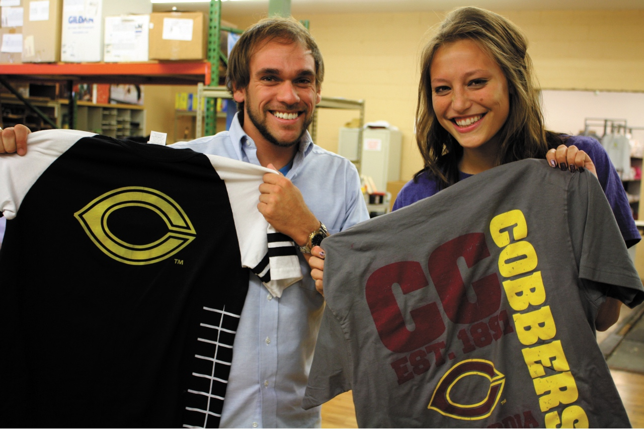 Photo by Rachel Torgerson. 2010 Concordia graduates Brandon Huether and Anna Hagen show off some of the t-shirts they have helped design due to their work with Old Lutheran, a company in Moorhead that creates unique products that help customers express their Lutheran identity.