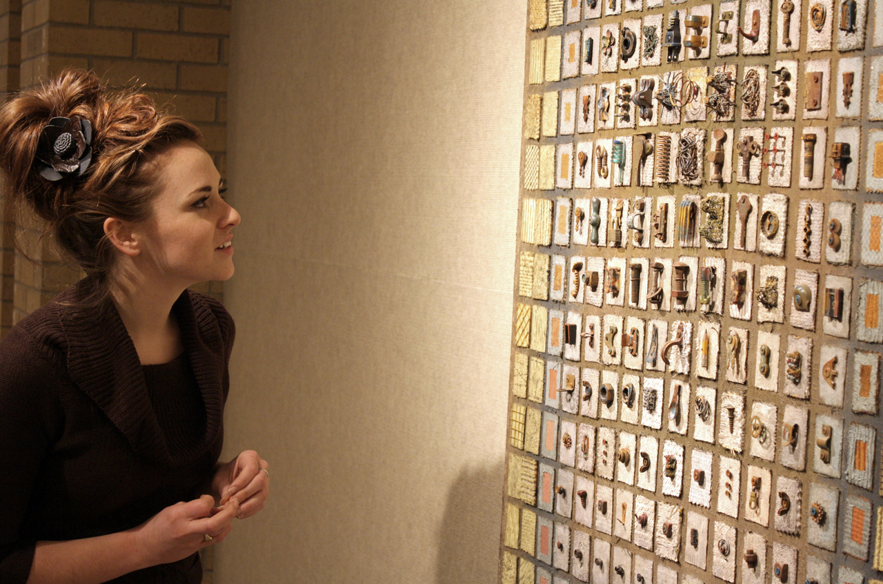Photo by Rachel Torgerson. Senior Ashley Dedin admires some of the work done by faculty member Mike Marth of Concordia's art department, during the Annual Faculty Art exhibition Jan. 17.