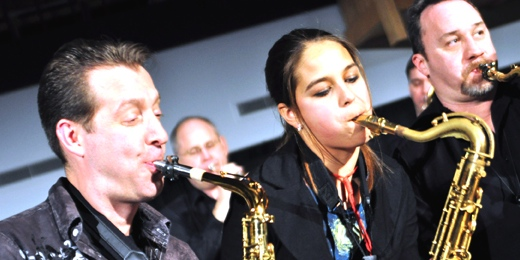 Photo by Rachel Torgerson. Members of Post Traumatic Funk Syndrome, Russ Peterson and Matt Patnode, play sax with prospective student Sarah Kremer.