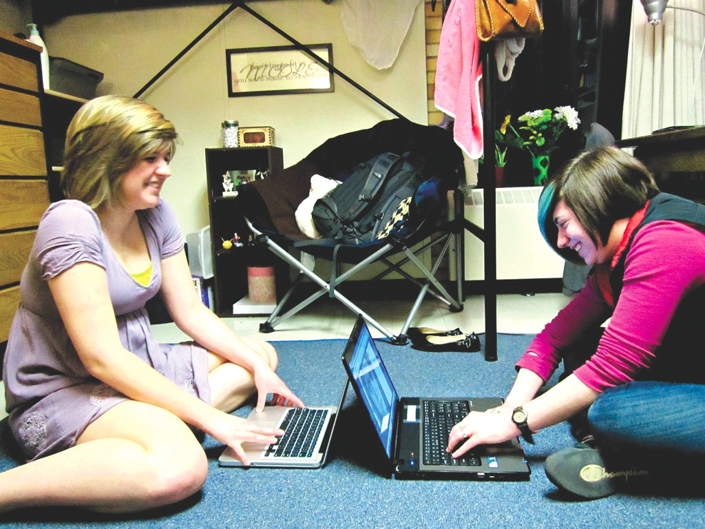 Photo by Meg Pittelko. Nicole Kippen and Megan Schindler catch up on their friends' blogs in Kippen's room in Hoyum Hall. Both girls maintains their own blogs.