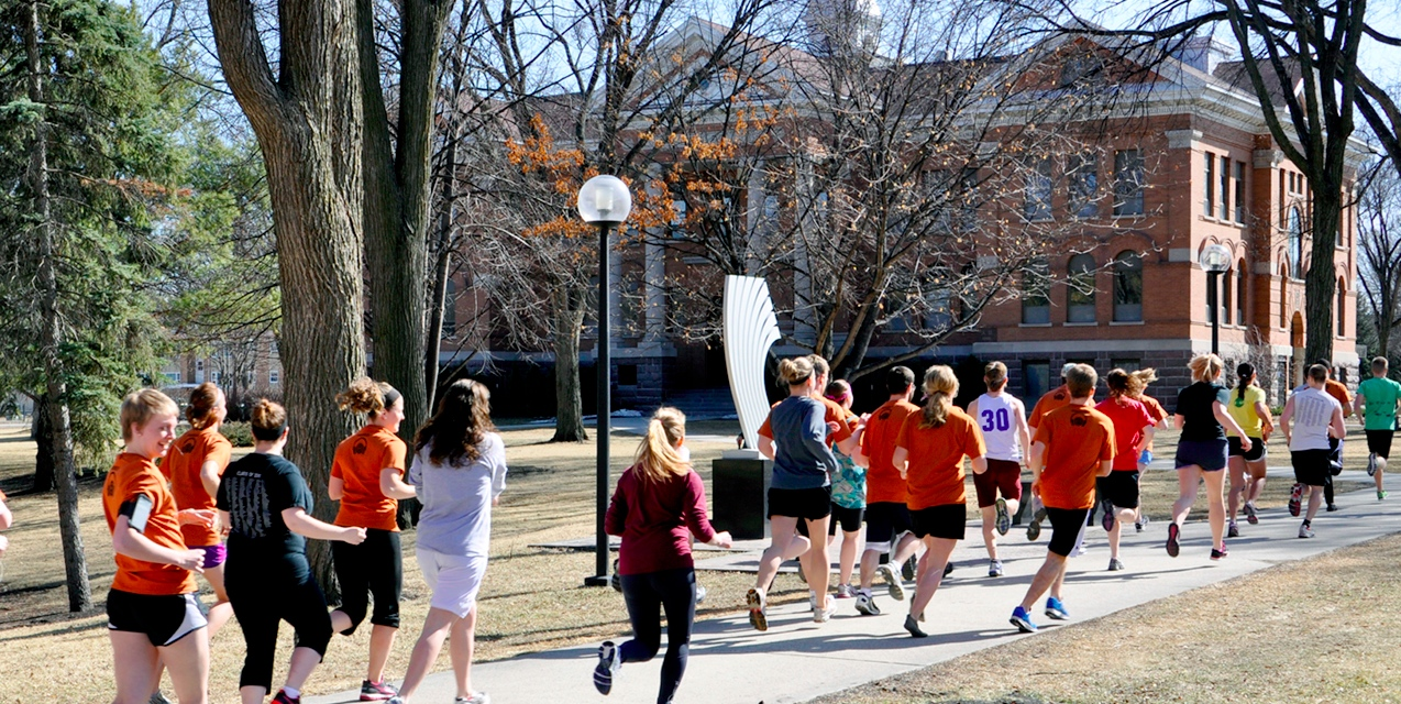 Photo by Melisa Barish. Cobbers run through the campus as part of CEC's first annual Pi Day Fun Run.
