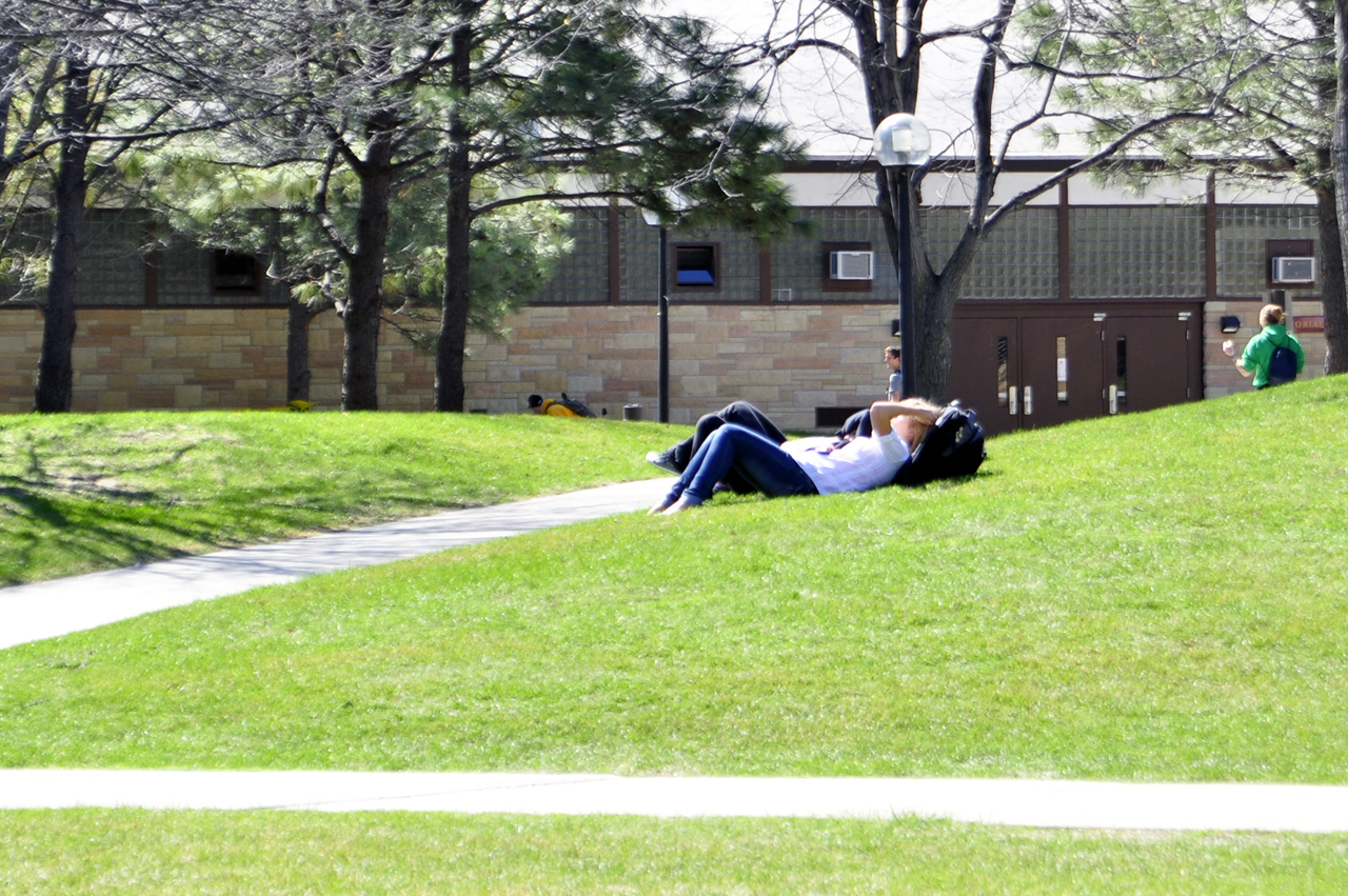 Photo by Olivia Gear. Students relax and soak up the sun Olin Hill. The hill becomes a popular favorite of students on warm spring days when it comes to relaxing or playing games.