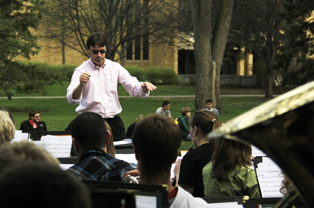 Photo by Rachel Torgerson. Nathaniel Dickey directs the Symphonic Band at their Earth Day concert outside of Francis Frazier Comstock Theatre. This is the first outdoor Earth Day concert the department has performed and was seen as a success by students and faculty.