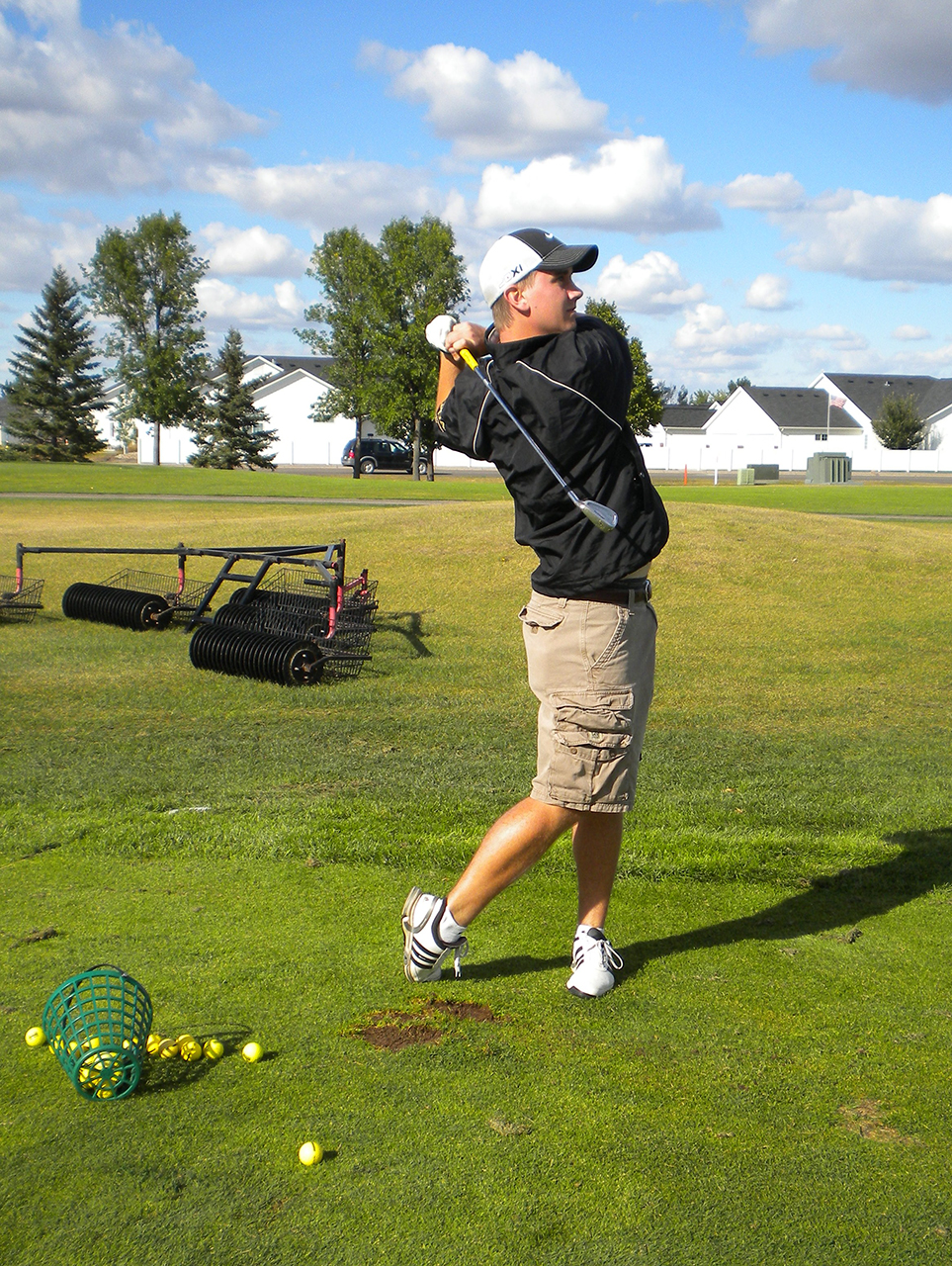 Photo by Jamie Telander. Golfer Andrew Whitchurch tees off at practice.
