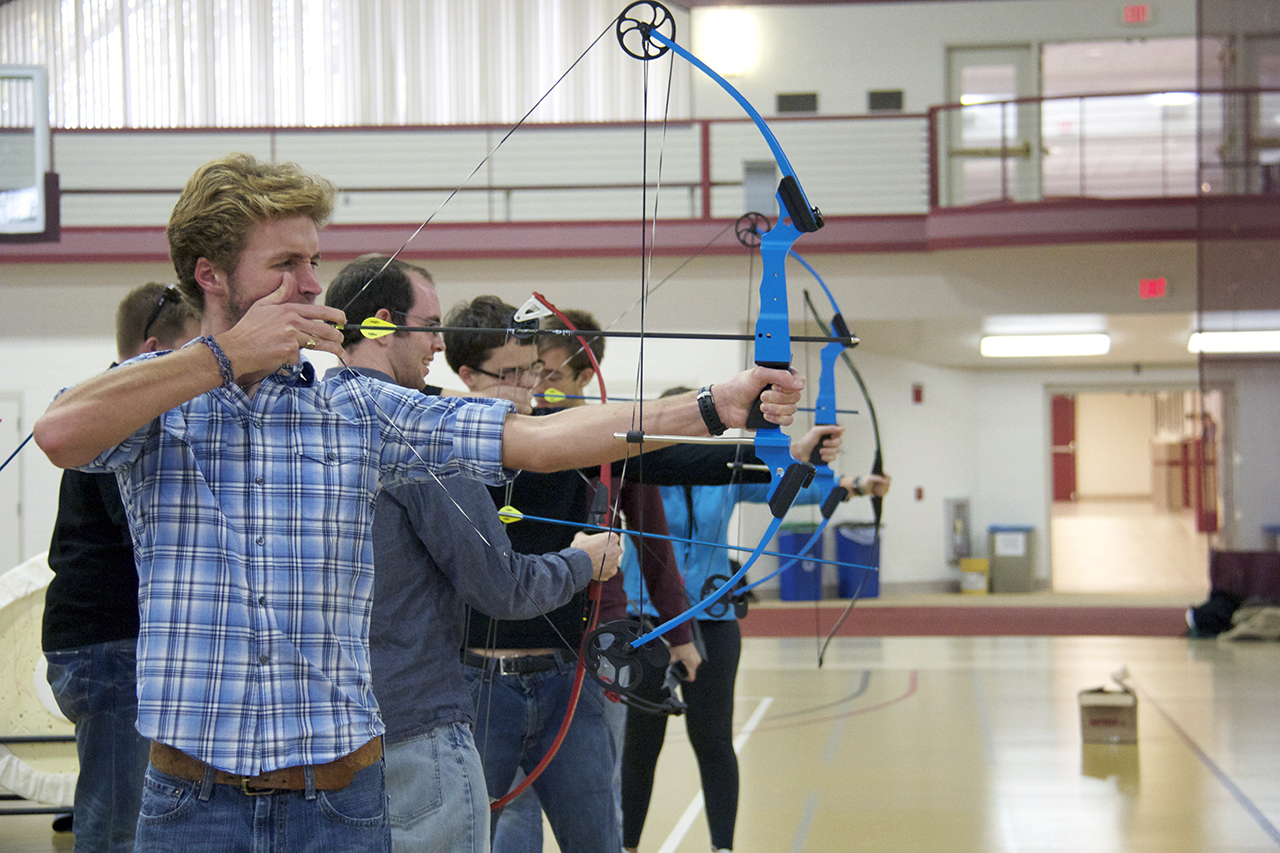 Photo by Jamie Telander. Soren Poffenberger, Concordia 2013, aims at his target in the archery wellness course.