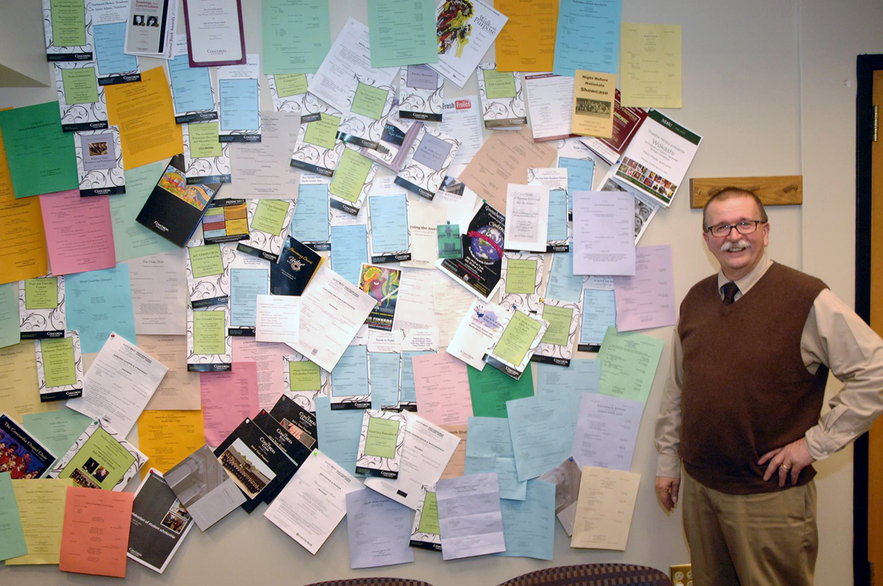 Photo submitted. Bruce Vieweg, chief information officer and associate provost, smiles next to his office wall covered in programs from the music events he attended in 2011. Vieweg sends personalized messages to performers to praise them for their art.