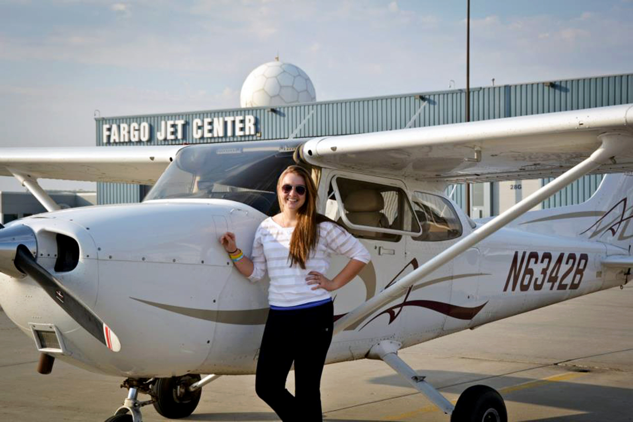 Photo by Marisa Jackels. Heidi Thom poses next to the plane she flew at the Fargo Jet Center.
