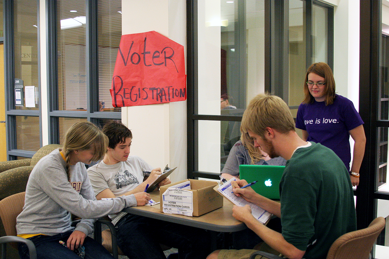 Photo by Kaia Miller. Concordia students take a minute to become registered voters at the booth in the Parke Student Leadership Center, facilitated by the Campus Democrats.