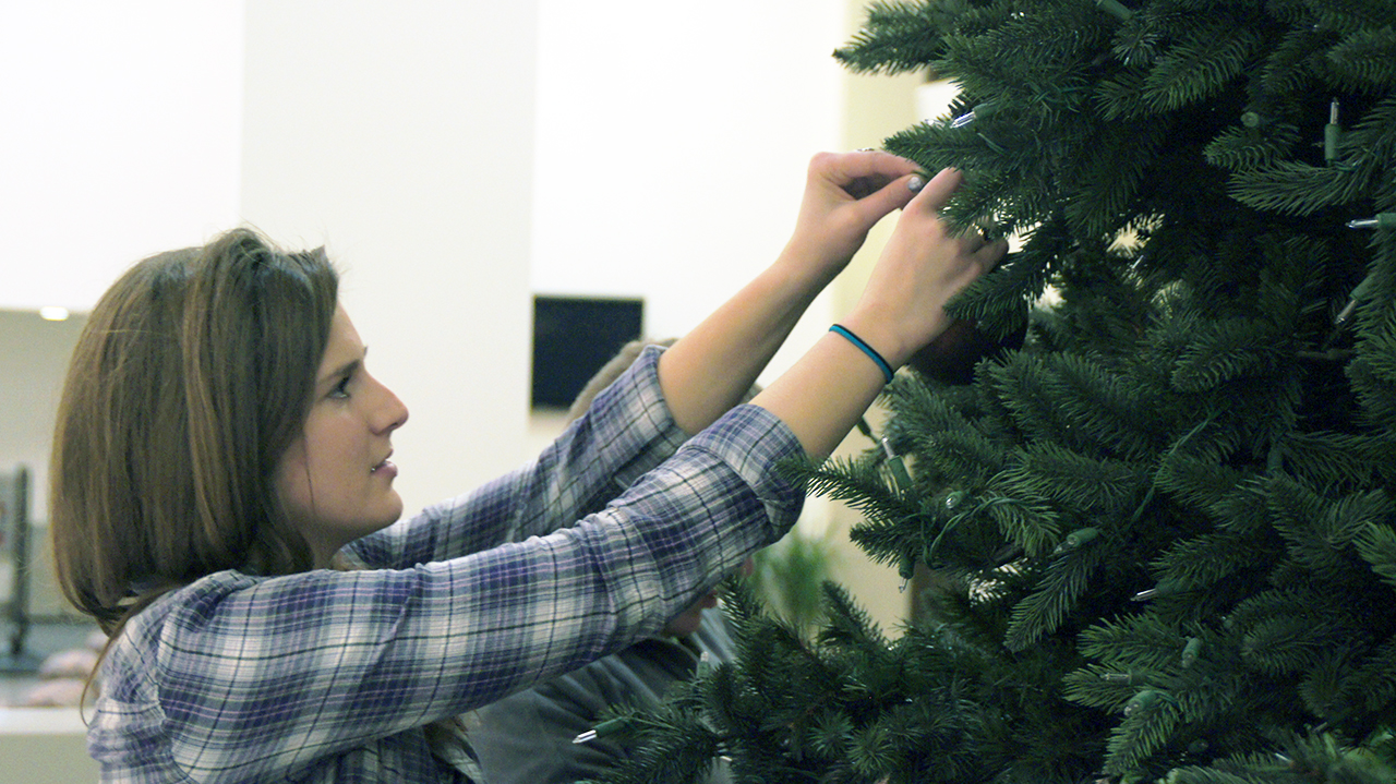 Photo by Paul Flessland. Jocelyn Fetsch, SIC Commissioner, hangs an ornament on the campus center Christmas tree.
