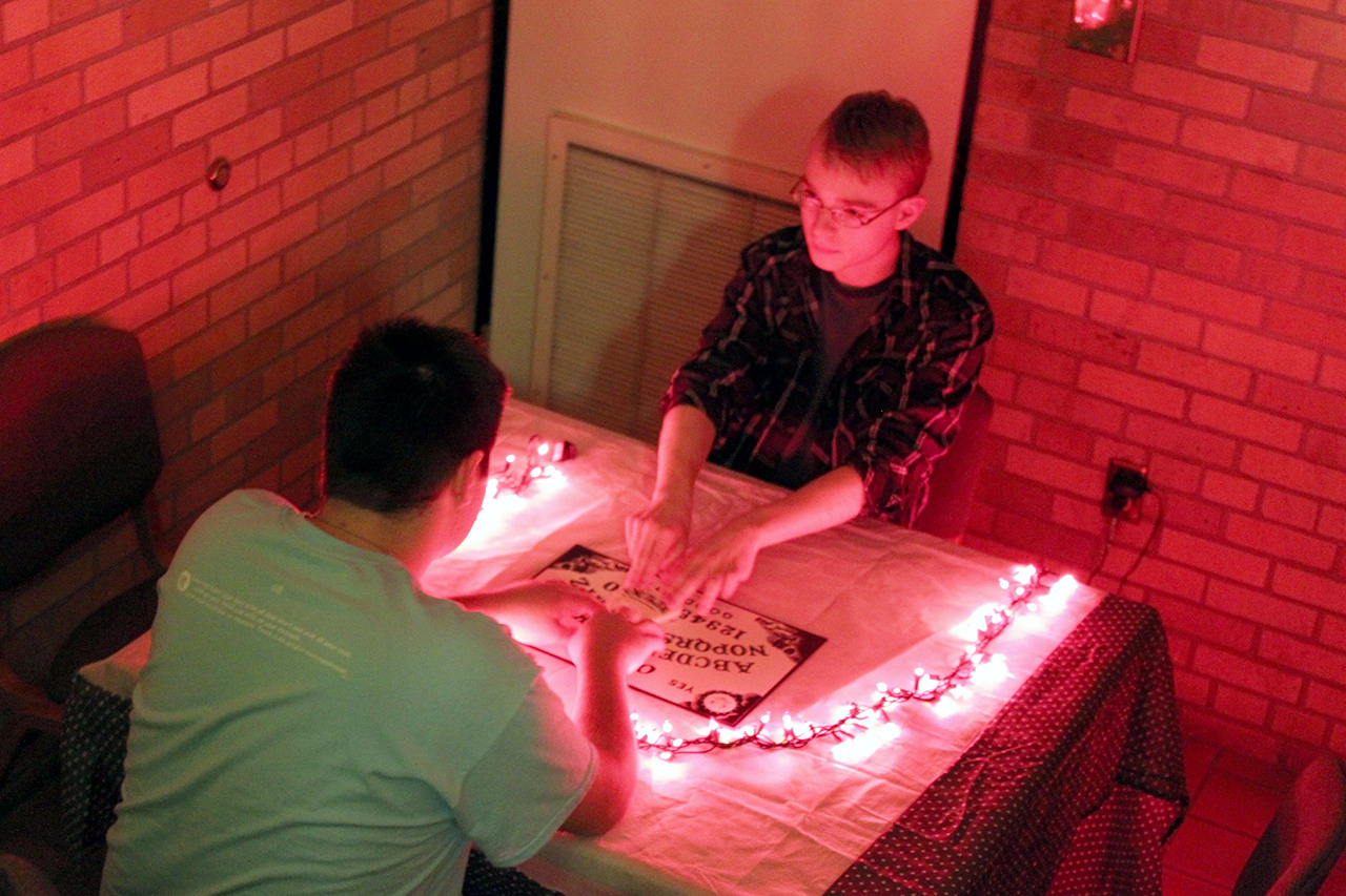 Residents Matthew Burian and Alexander Hagen try out the Ouija board provided in Livedalen's haunted maze.