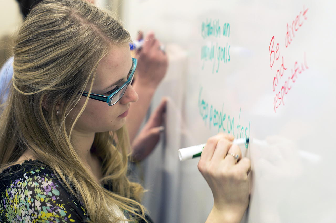 Photo by Paul Flessland. Becca Asheim writes her thoughts on the white board during a LeadNow session.