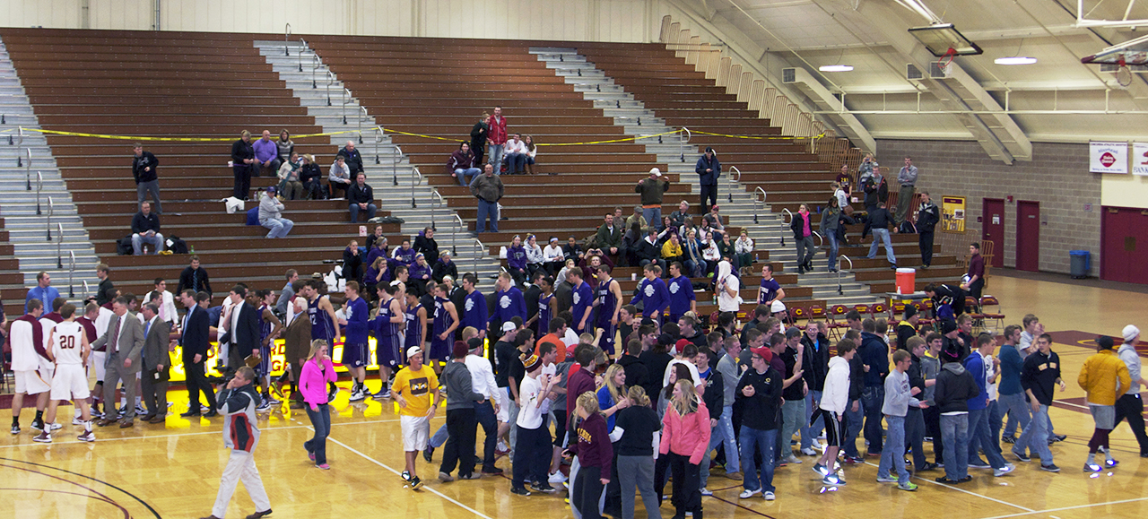 Photo by Ali Everts. Fans and players swarm the court after the men's basketball team defeated Division III No. 1-ranked St. Thomas. This week was full of successes for basketball, with the women's team asending to the No. 1 spot in the MIAC.
