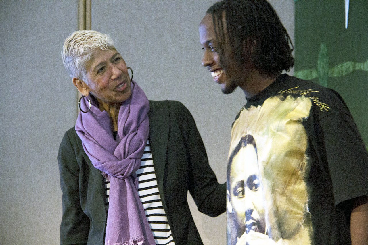 Photo by Olivia Gear. Ericka Huggins, a former Black Panthers leader, laughs with Alexandre Cyusa Ntwali during her keynote presentation on Martin Luther King, Jr. Day, Jan. 21.