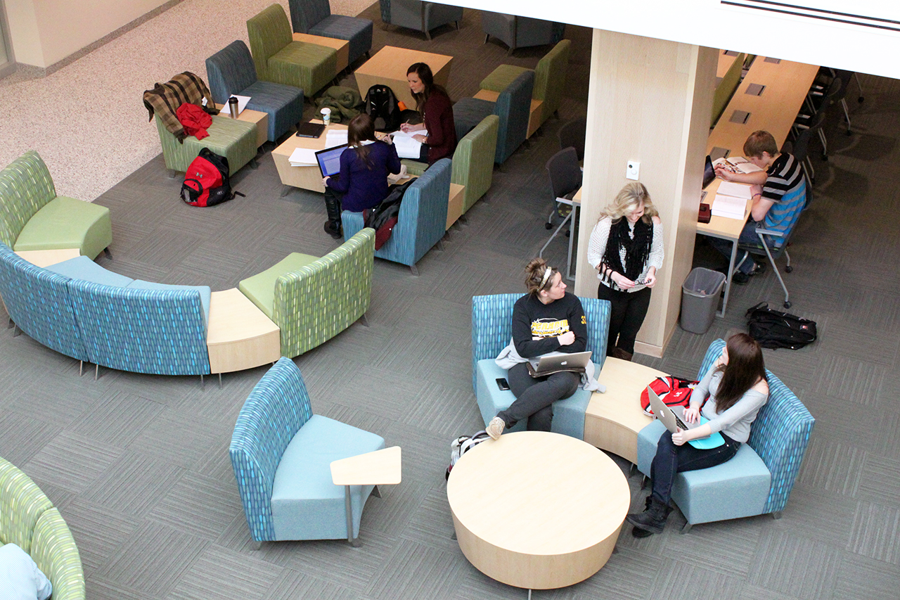 Photo by Mary Henning. Students gather in the basement-level lounge at the newly rennovated Grant Center, home now to the Offutt School of Business.