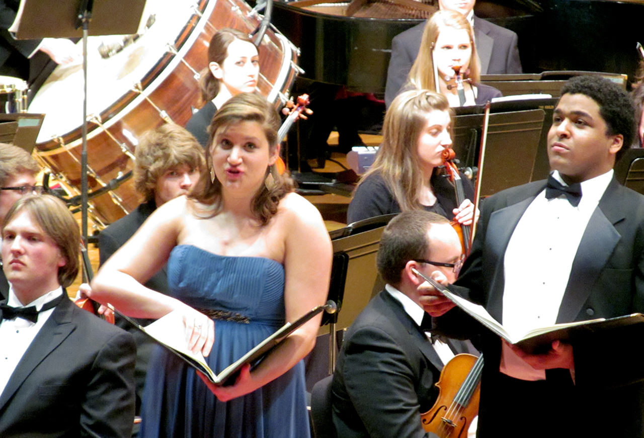 "Justine Scarbrough and Christopher Kenney sing ""Tempus Est Locundum"" in front of the orchestra during the performance."