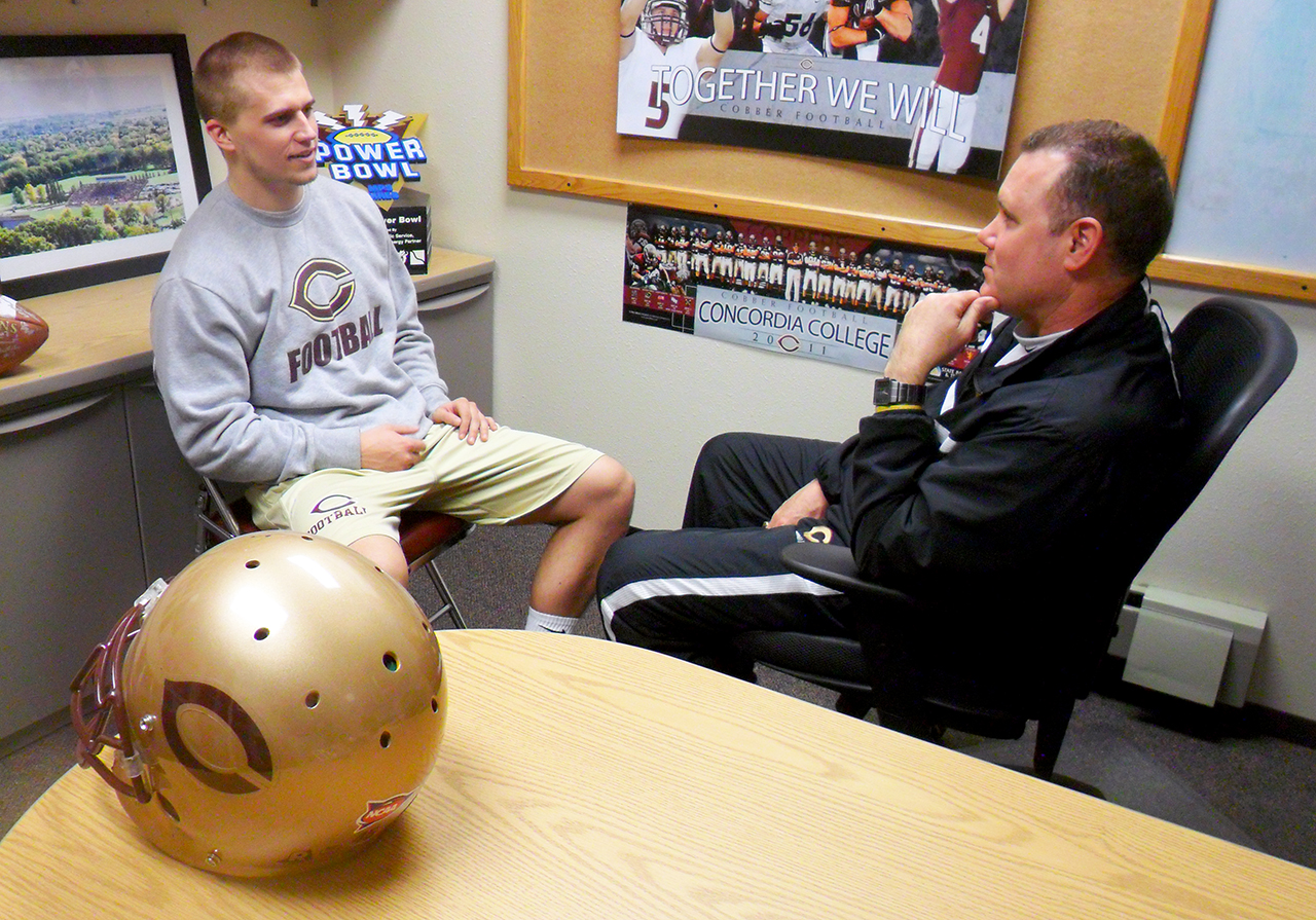 Photo by Jen Swenson. Head football coach Terry Horan chats with junior running back Matt Peterson, who Horan recruited three years ago. Peterson said that he was impressed by the time and individual attention he received from Horan and other athletic recruiters at Concordia and said that this was a major contributing factor in why he chose to become a Cobber athlete.