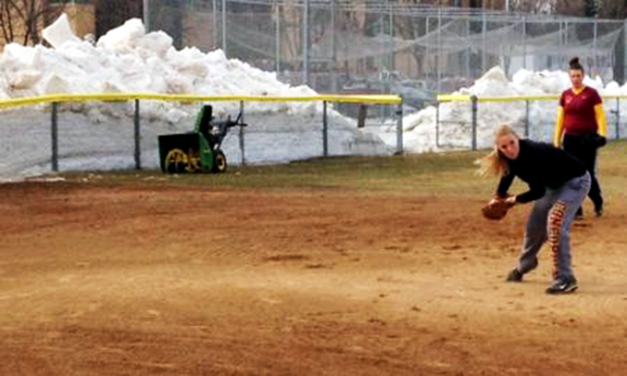 Submitted photo. A giant snow embankment surrounds the softball field during a recent practice. Though the team was  able to clear the field of snow for this particular practice, their season has been hindered by incliment weather conditions.