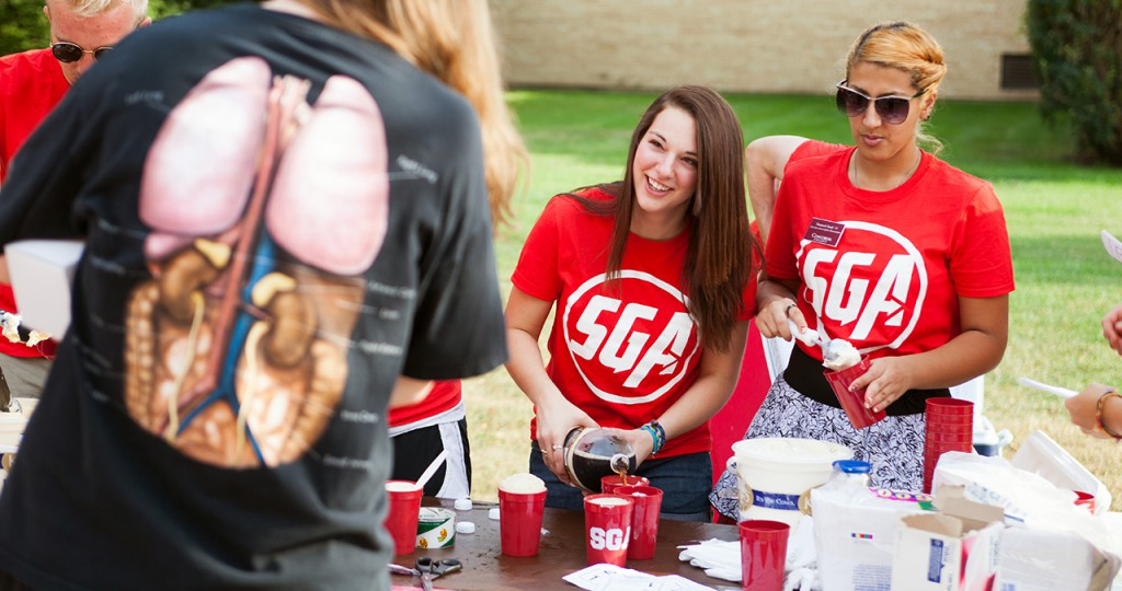 SGA members Carly Grandner and Hananeh Saedi prepare root beer floats at Cobber Expo. Photo by Chase Body.