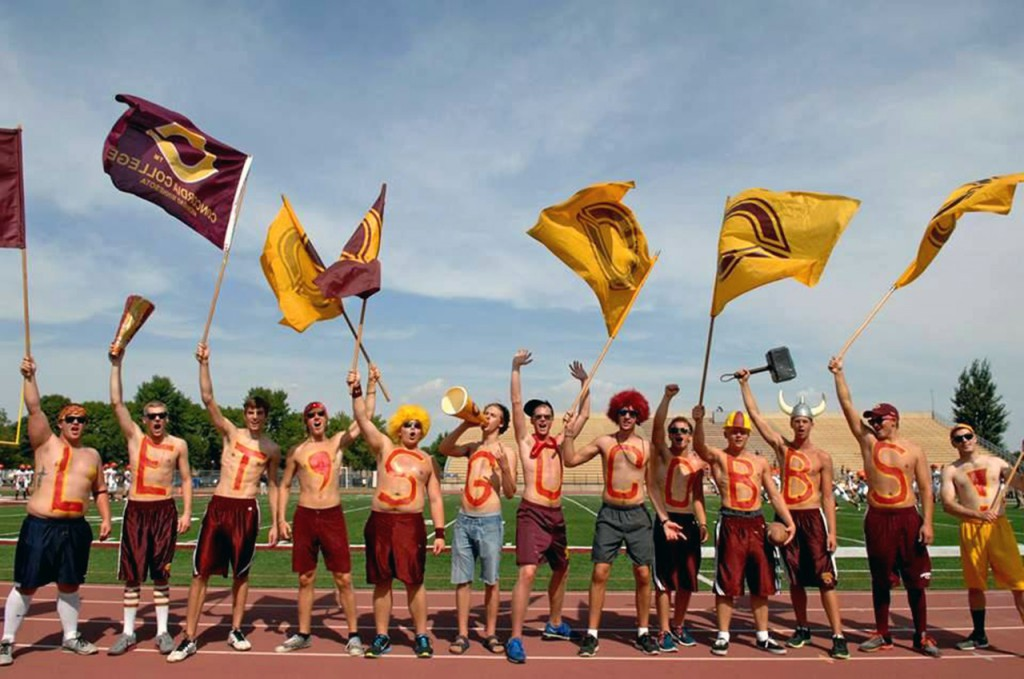 "Cobber Nation gets the crowd revved up at a Cobber football game spelling out, ""Let's Go Cobbs!"" on their chests and waving Concordia flags. Submitted photo."