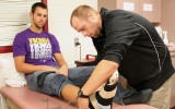 Athletic trainer Max Pagel works on senior Mark Whiting's injury in the athletic training office. Photo by Mary Henning.