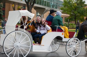 Homecoming King and Queen Colin Sullivan and Carly Grandner ride in the homecoming parade Sauterday, Oct. 12. Despite the dreary weather, the parade still represented a large portion of the campus community with around 100 floats. Photo by Chase Body.
