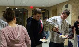 Kristin Remick serves pancakes to students attending pancake feed in East Complex. The feeds served as a fundraiser for Fill the Dome, as students were asked to bring canned goods to donate. Photo by Chase Body.