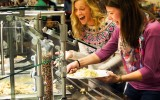 Concordia students Brenn Kjellberg and Erin Thompson dish up at the Thanksgiving-themed meal in Anderson Commons. Photo by Morgan Schleif.