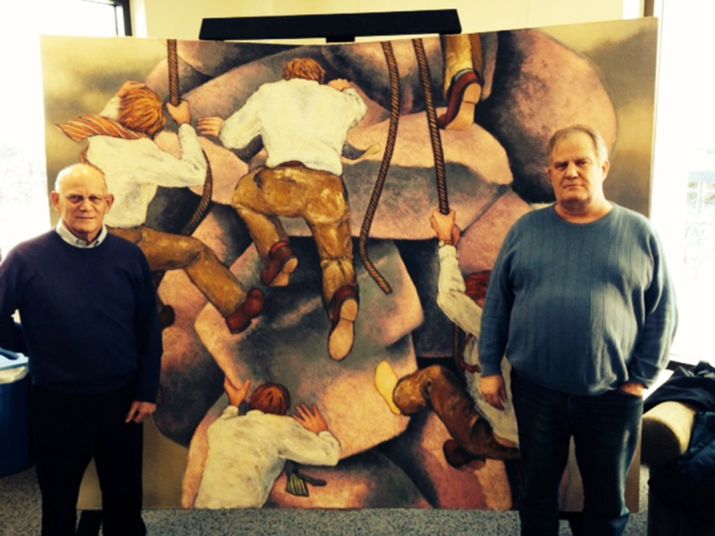 "Cobber alums and brothers Mark Budd (left) and Eric Budd (right) stand in front of Eric's painting ""The Rock Climbers."" Mark donated the painting to the college after he returned to Concordia last spring and saw the art lining the walls of the Offutt School of Business. Submitted photo."