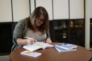 Collins delves into the books of her new major, heritage and museum studies. Photo by Maddie Malat.