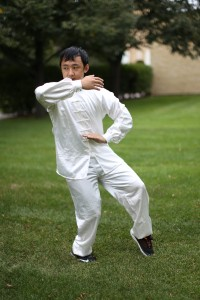 Senior Xao Vang practices Tai Chi for a symposium session. Photo by Maddie Malat.