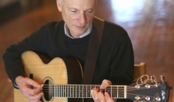 Dr. Bill Snyder strums his guitar and prepares a few pieces for his Nichole's Pastry performance. Photo by Maddie Malat.