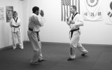 Master Dave Schimmelpfennig instructs Stephen Oppegaard on the practices of taekwondo. Photo by Maddie Malat.