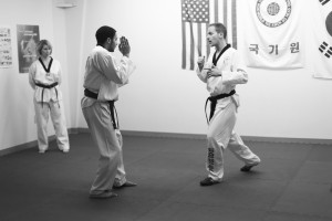 Master Dave Schimmelpfennig instructs Stephen Oppegaard on the practices of taekwondo. Photo by Maddie Malat.