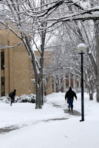 Student rushes to class as Concordia staff member shovels fresh snow. Photo by Hans K. Peter.