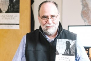 "Scott Olsen displays his new book, ""A Moment With Strangers."" Photo by Emely Kransvik."