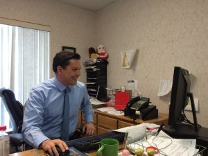 Chris Berg sits at his desk at the KVLY office. Photo by Marit Johnson.