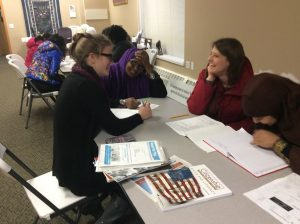 Women helping each other to study for the citizenship tests at the WE center. Photo by Paige Olson.
