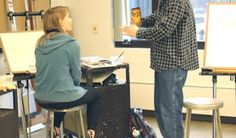 David Boggs gives advice on watercolor painting techniques to one of his students, Helena Langr. Photo by Maddie Malat.