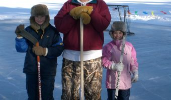 Young Jake and Maddie Ellingson on the ice with their father. Photo courtesy of Kim Ellingson.
